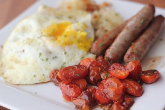 Oven Roasted Tomatoes with Onion Hash, Fried Egg, and Sausages