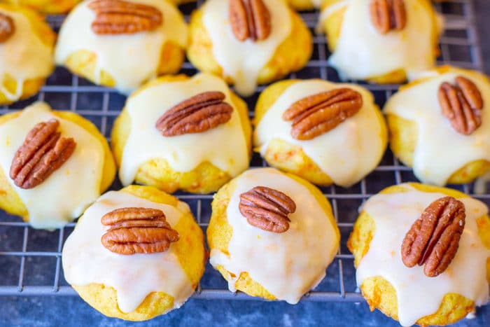 Carrot cookies with orange icing and a pecan halve on a rack