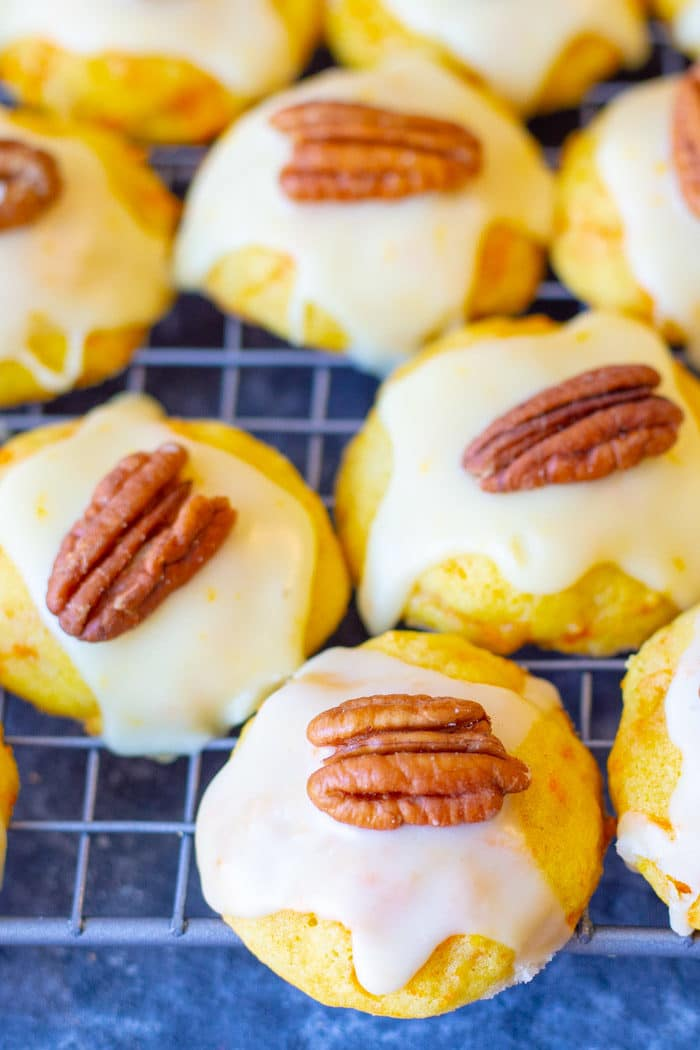 Carrot cookies with orange icing lined up and topped with a pecan halve