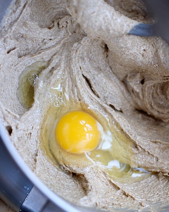An egg being added into creamed butter and sugar for cookies