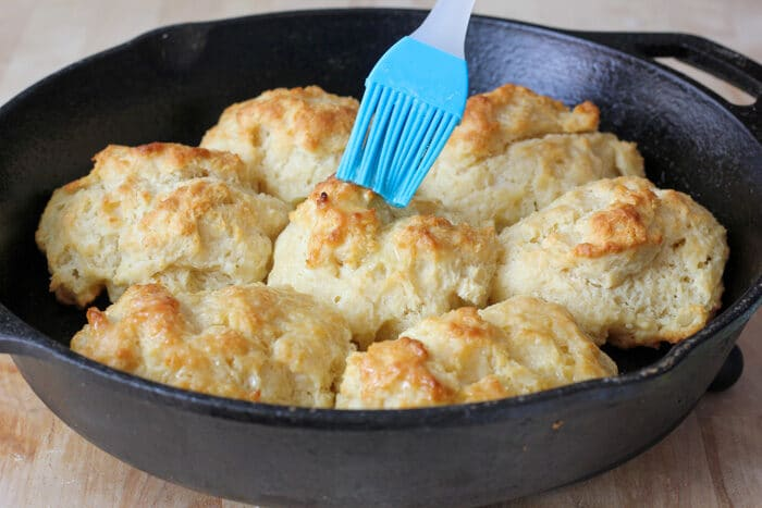 Baked drop biscuits in a skillet being brushed with melted butter.