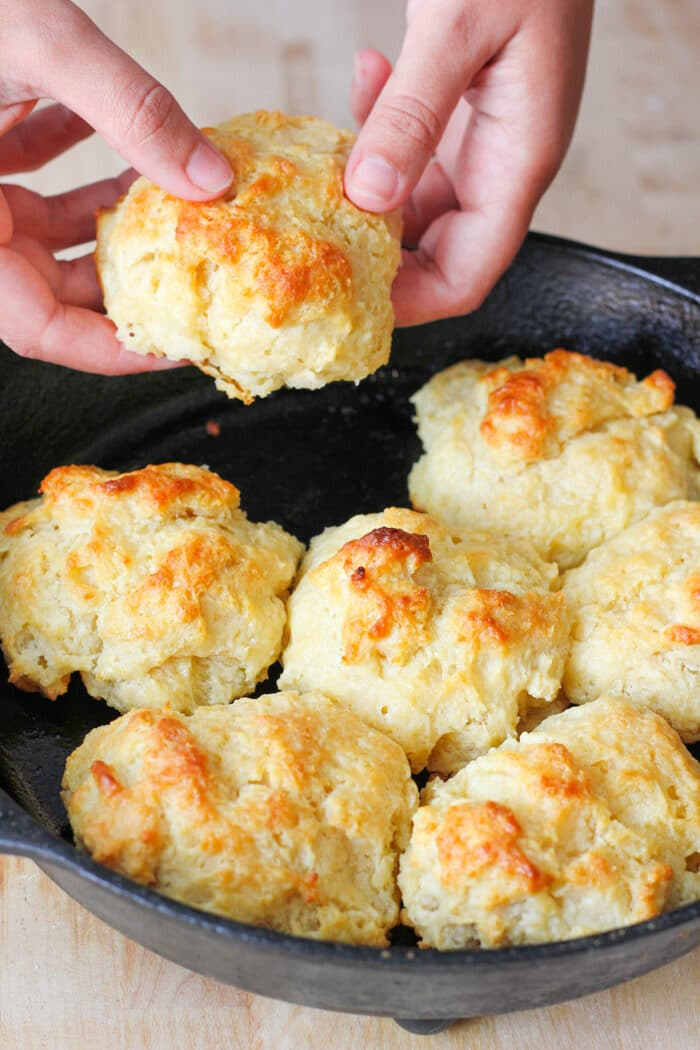 Easy drop biscuits in a cast iron skillet after being baked. One is being picked up to be eaten.