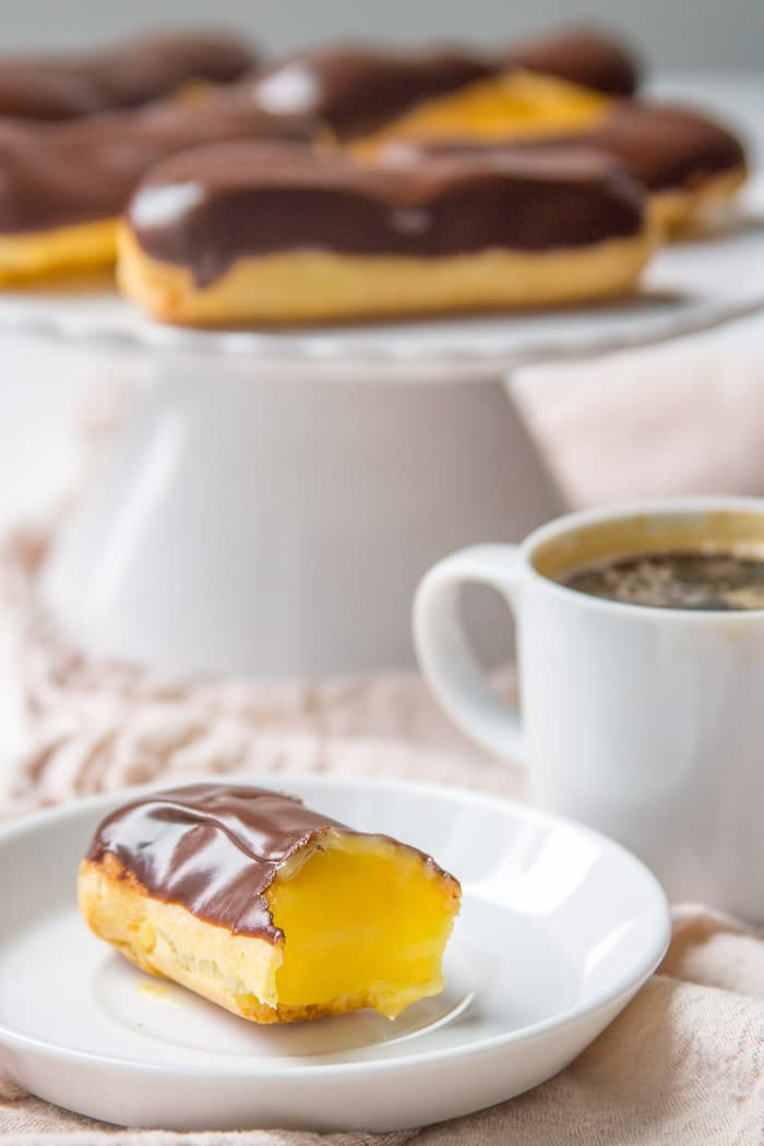 Chocolate eclair with a bite taken out with a platter of eclairs