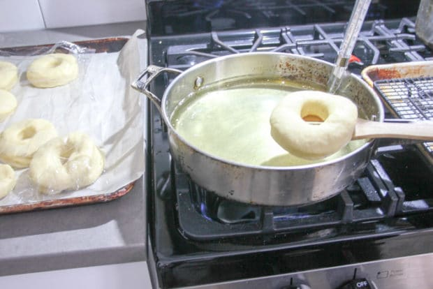 Pot of oil on stovetop, donut carefully placed in