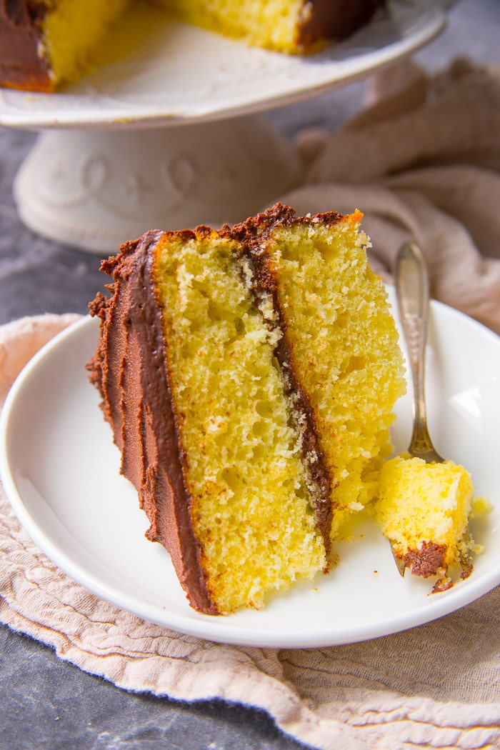 Slice of the best yellow cake with whipped chocolate ganache frosting