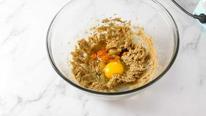 Adding orange zest and egg to bowl for cranberry white chocolate cookies