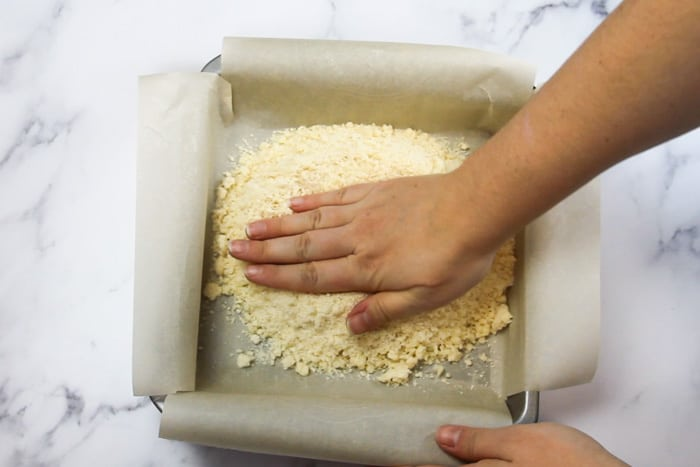 Patting the shortbread crust into the pan