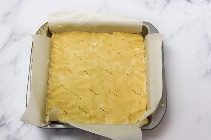 Shortbread crust after being docked and ready to bake