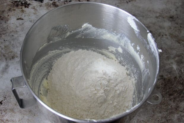 Adding flour into shortbread cookie dough