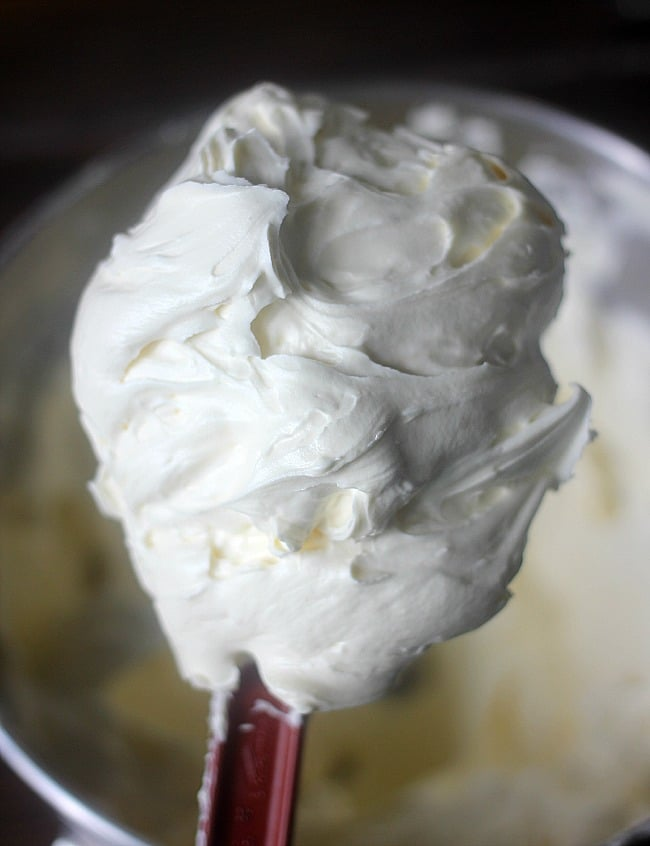 Rubber spatula with a big scoop of cream cheese frosting on it