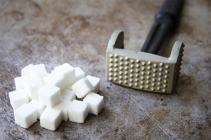 Sugar cubes and a meat mallet used to make homemade pearl sugar