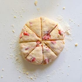 Strawberries and cream scones dough shaped into a circle and cut into 8 wedges