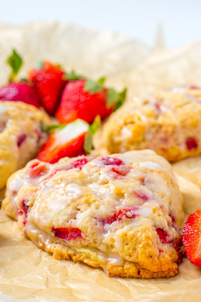Strawberries and cream scones laying on parchment paper