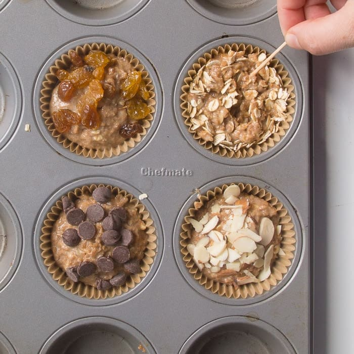 Refrigerator bran muffin batter with various mix-ins being added such as raisins, rolled oats, chocolate chips, and almonds.