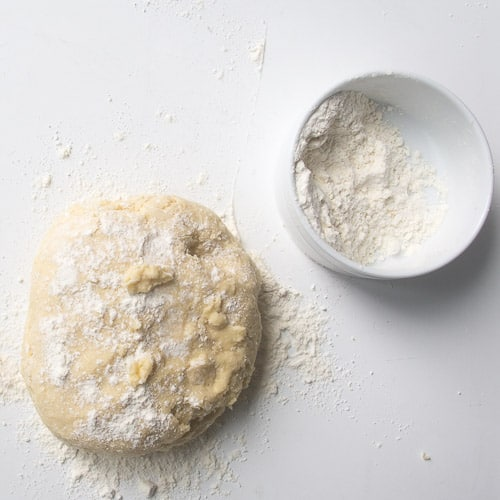 Dough before its kneaded on counter with extra flour on top and surface
