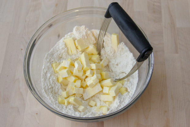 Butter cubes in bowl with dry ingredients, pastry cutter on side