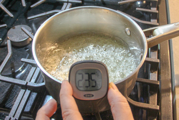 Taking the temperature of sugar syrup in pan, it's 235 degrees F