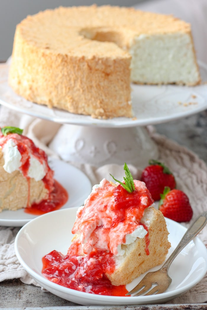 A piece of angel food cake topped with fresh strawberry sauce and a mint sprig, sitting in front of the cut-into angel food cake on a cake stand