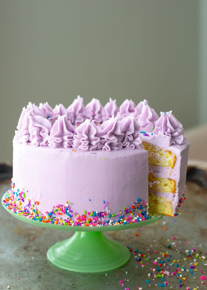 A 3 layer yellow cake that is frosted with purple icing and decorated with colorful sprinkles. The cake is on a green cake stand and a piece is cut showing the inside.