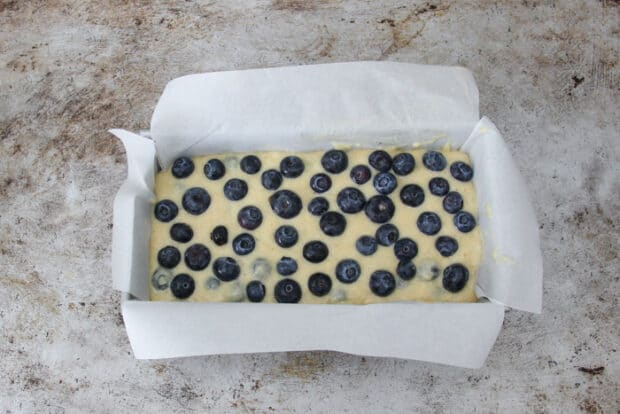 Raw batter in loaf pan with blueberries on top before being baked