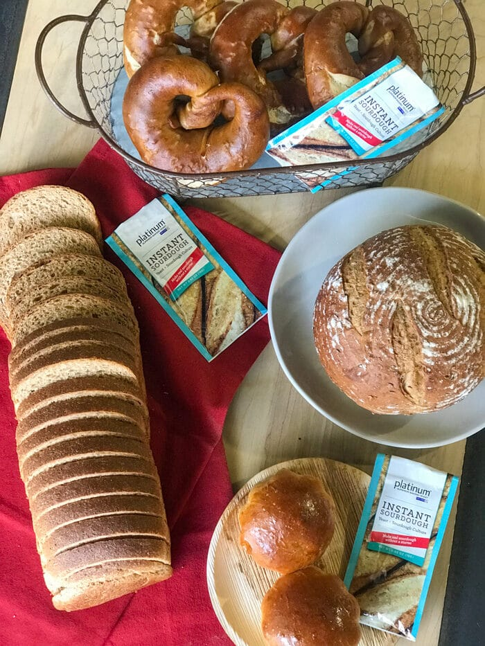 A variety of breads made with platinum instant sourdough yeast- pretzels, a boule, brioche rolls, and a sandwich loaf
