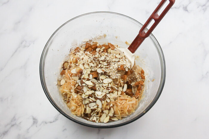 Adding shredded apple, caramel pieces, and slivered almonds into cookie dough.