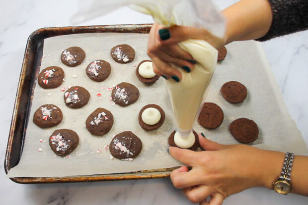Squeezing peppermint buttercream out of a pastry bag onto the baked chocolate whoopie pie cookie