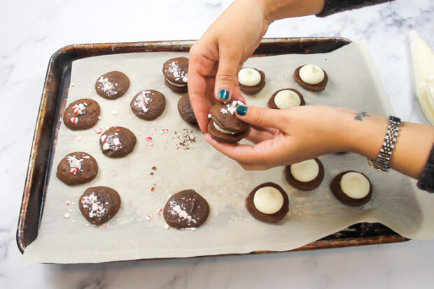 Closing the two whoopie pie ends together, sandwiching the peppermint filling