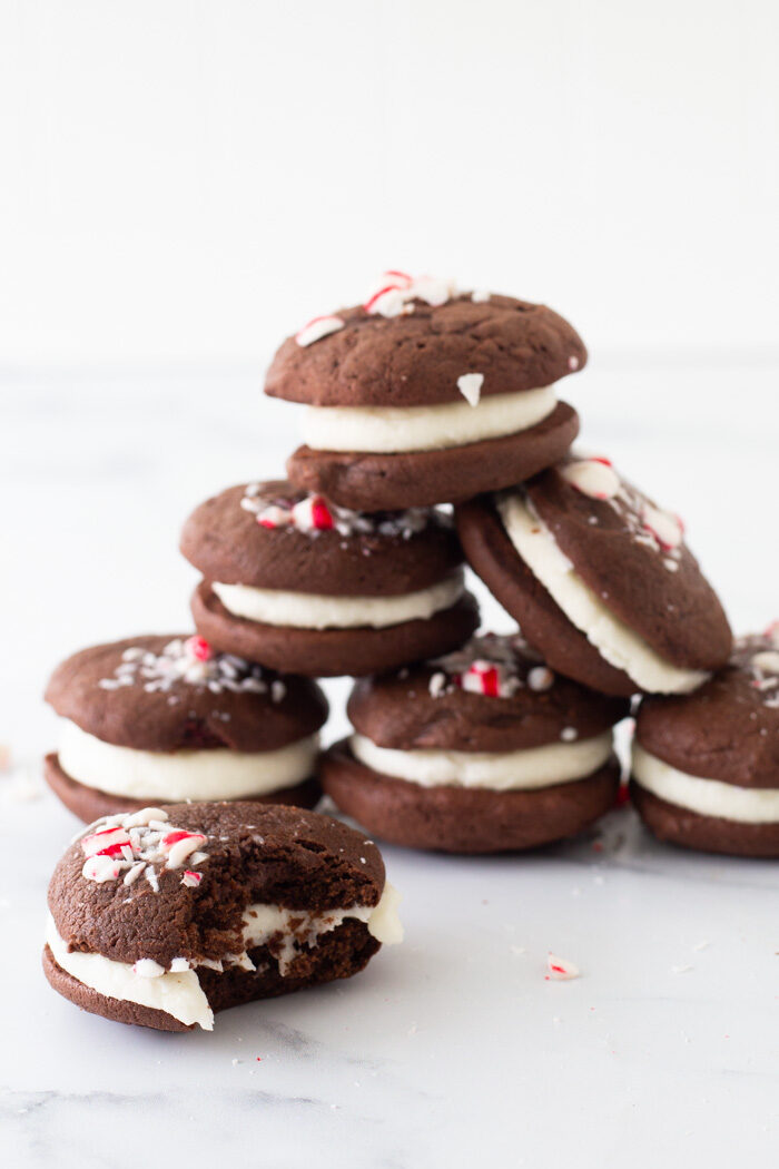 Tower of chocolate peppermint whoopie pies sitting on a marble platter. One cookie in front has a bit taken out of it