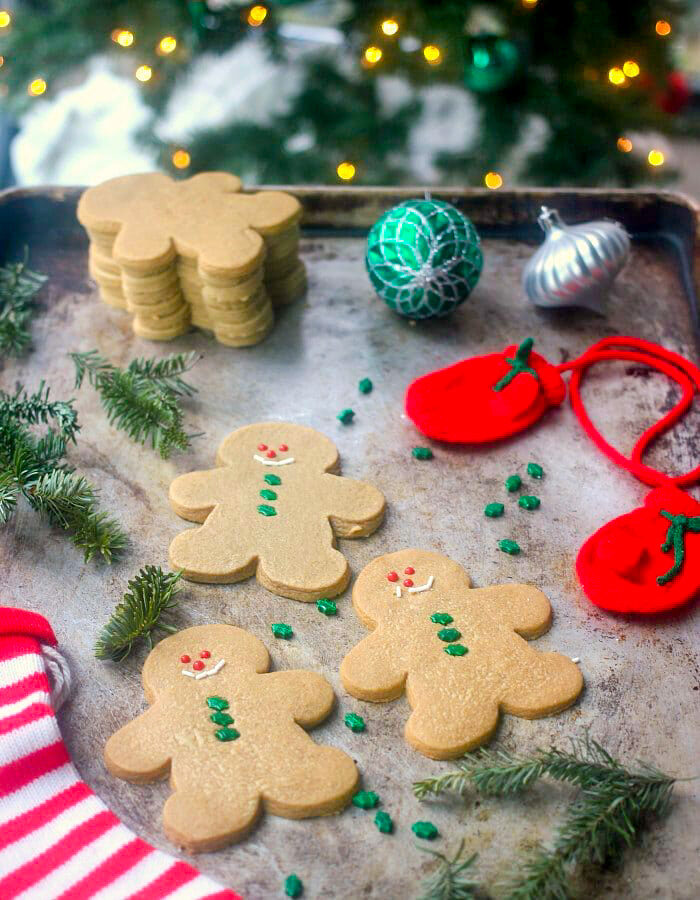 Baked gingerbread cookies lined up on a sheet pan with christmas decorations spread around on the pan