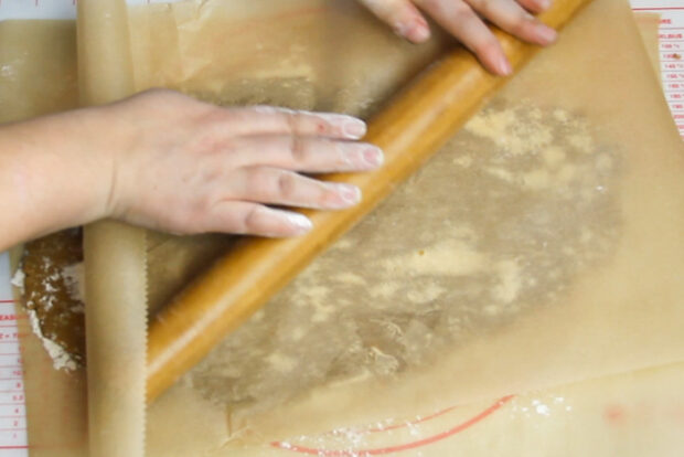 Rolling out gingerbread dough between two pieces of parchment paper