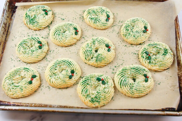 Baked spritz cookies after holly berry sprinkles have been pressed in
