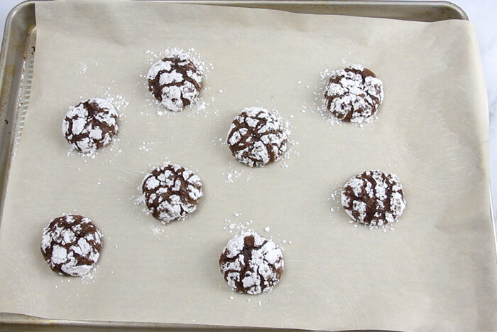 Tray of baked chocolate crinkle cookies right after coming out of the oven.