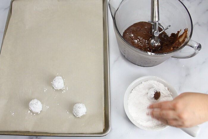 Rolling chocolate crinkle cookie dough into powdered sugar to coat.