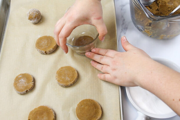 Pressing gingersnap cookie dough down with a glass before baking