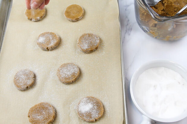Sprinkling more granulated sugar on shaped gingersnap cookies before baking