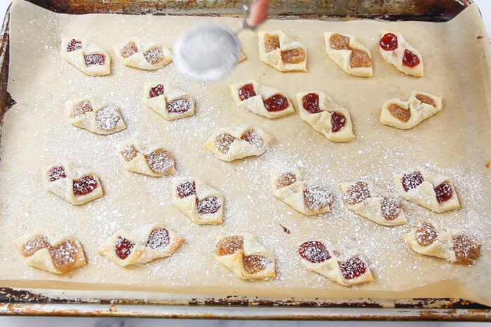Baked kolaczki cookies being dusted with powdered sugar