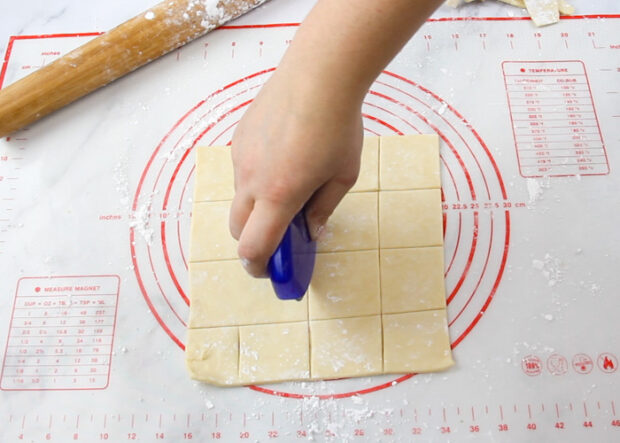 using a pizza cutter to cut out squares in kolaczki cookie dough