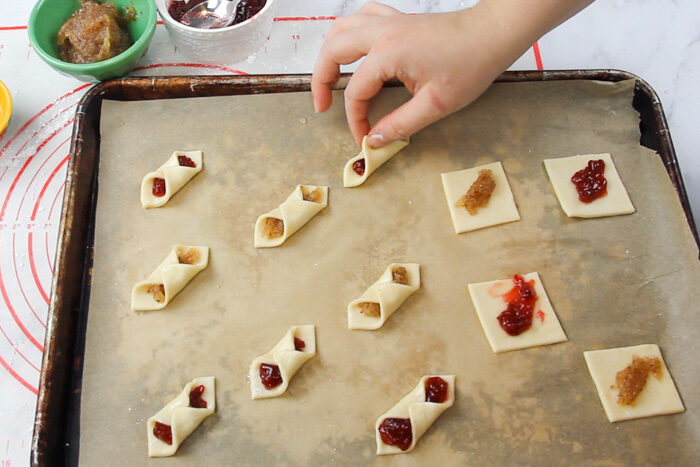 Pressing the edges of the kolaczki cookies together to seal before baking