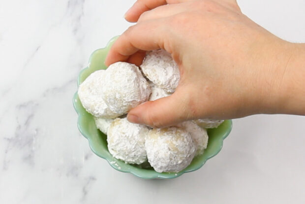 Bowl of finished pecan snowball cookies, one is being taken out of the bowl