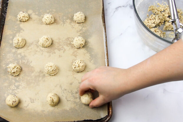 Rounding pecan snowball dough into balls and placing them back onto parchment lined baking sheet