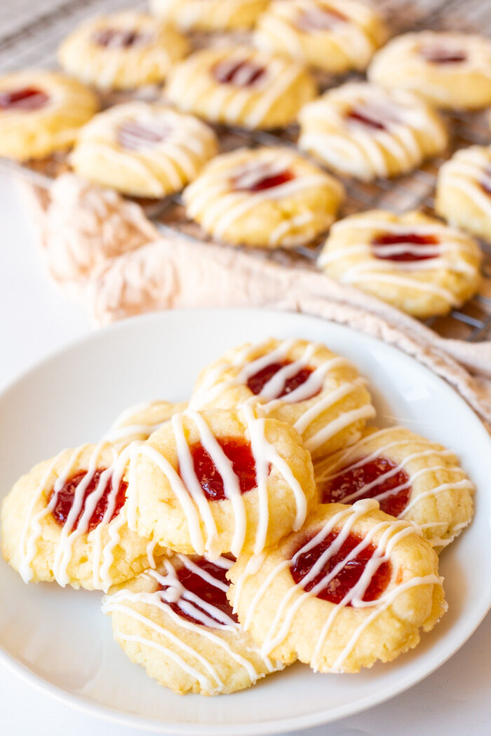 Plate of finished shortbread thumbprint cookies with a cooling rack in the background with cookies on top