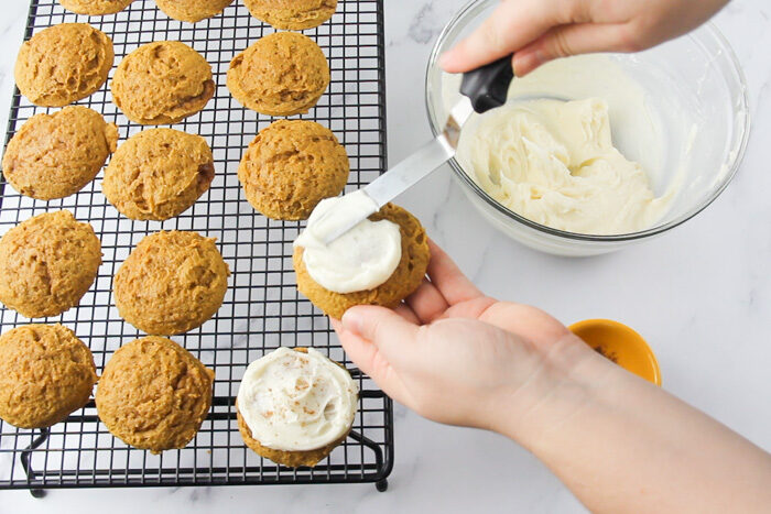 Frosting the soft pumpkin cookies with cream cheese frosting