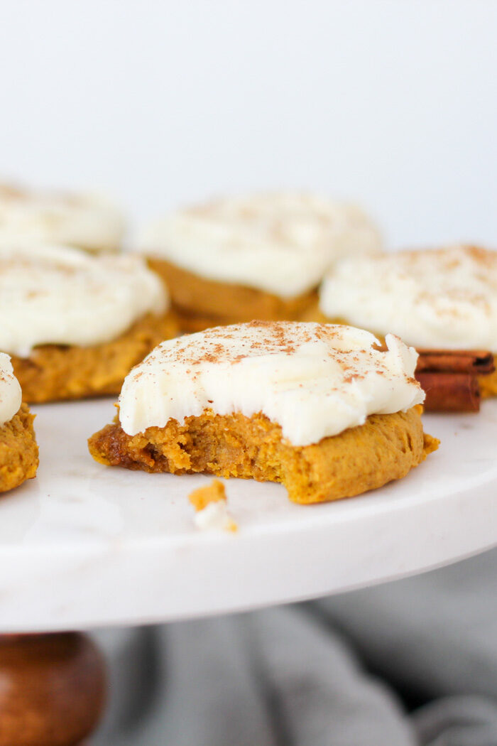 Soft pumpkin cookies on a tray. One has a bite taken out of it.