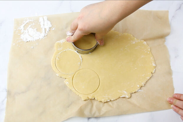 Rolled out cookie dough being cut by a round cookie cutter