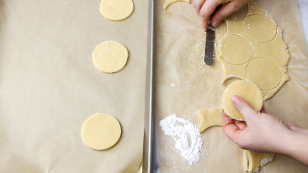 cookie dough that has been cut into rounds are being transferred onto a parchment lined baking sheet