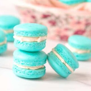 Stack of french macarons with a bowl of macarons in the back